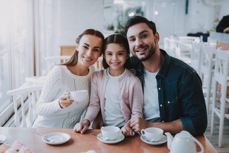 La familia joven está descansando en café imagen de archivo