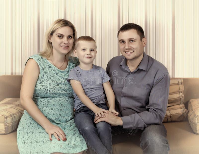 La familia joven está descansando en casa sobre el sofá Una madre embarazada, un pequeño hijo y un padre fotos de archivo