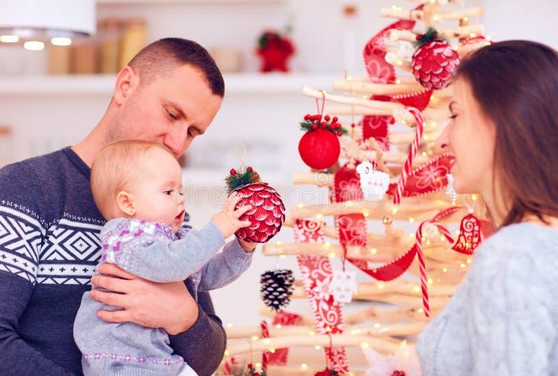 La familia joven feliz adorna el árbol de navidad del eco en casa fotos de archivo