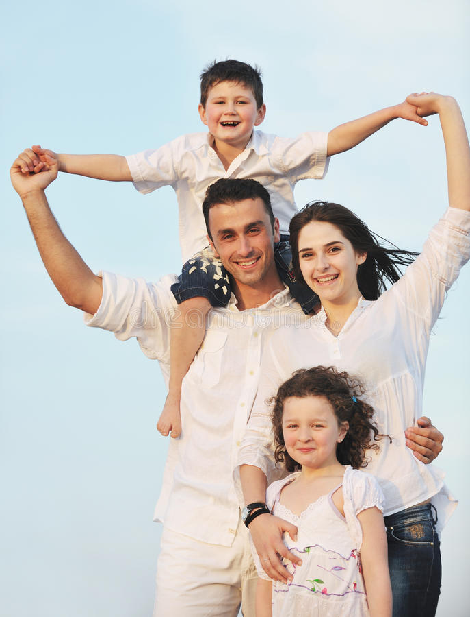 La familia joven feliz se divierte en la playa imagen de archivo