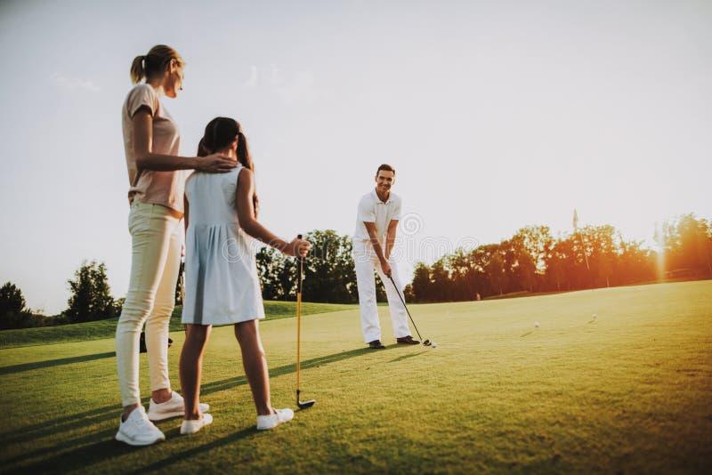 La familia joven feliz se relaja en campo del golf en verano foto de archivo libre de regalías