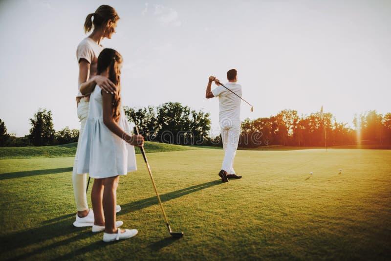 La familia joven feliz se relaja en campo del golf en verano fotografía de archivo libre de regalías