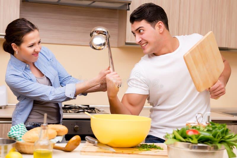 La familia joven que hace lucha divertida en la cocina imagen de archivo libre de regalías