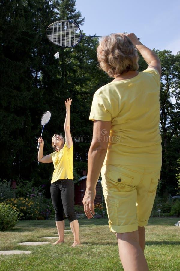 La familia juega a bádminton en el jardín fotos de archivo
