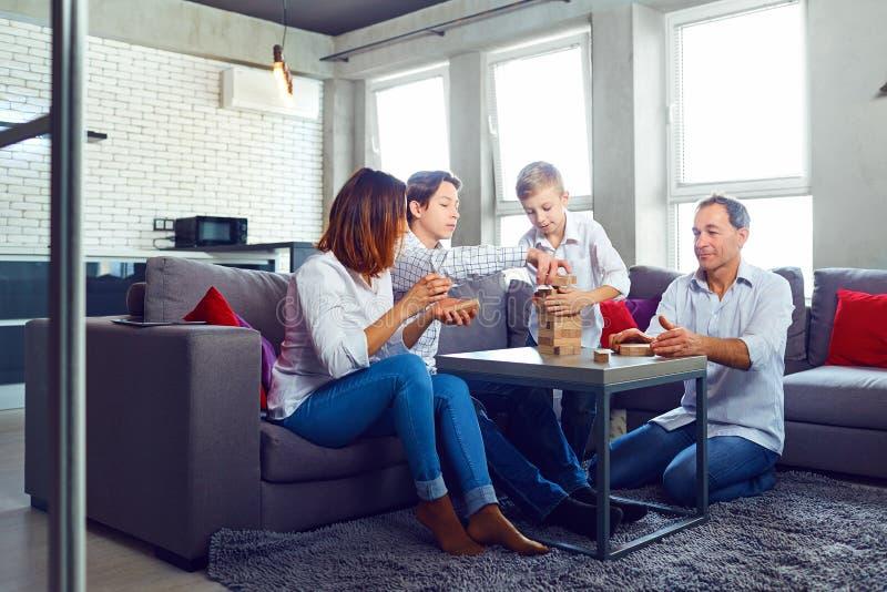 La familia juega a los juegos de mesa alegre mientras que se sienta en la tabla fotos de archivo libres de regalías