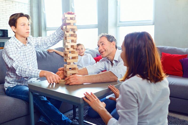 La familia juega a los juegos de mesa alegre mientras que se sienta en la tabla imagen de archivo