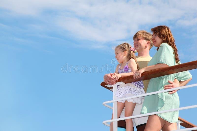 La familia la reclina en el mar y mira lejos del yate fotos de archivo libres de regalías