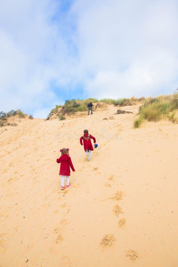 La familia, los padres y los niños están subiendo la duna de arena foto de archivo libre de regalías