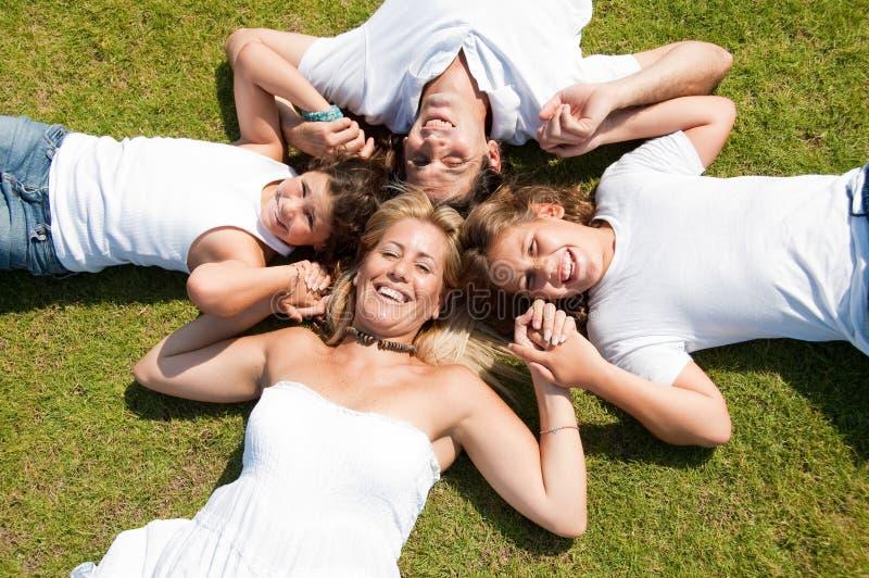 La familia miente en hierba imagen de archivo libre de regalías