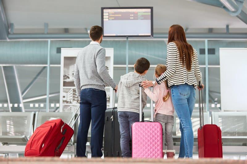 La familia mira en el marcador en el terminal de aeropuerto foto de archivo