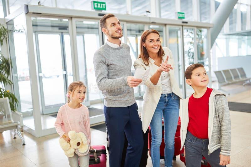 La familia mira a la puerta para su vuelo fotografía de archivo libre de regalías