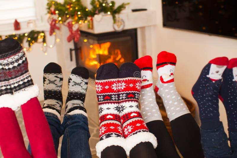 La familia moderna se está calentando cerca de la chimenea fotografía de archivo libre de regalías