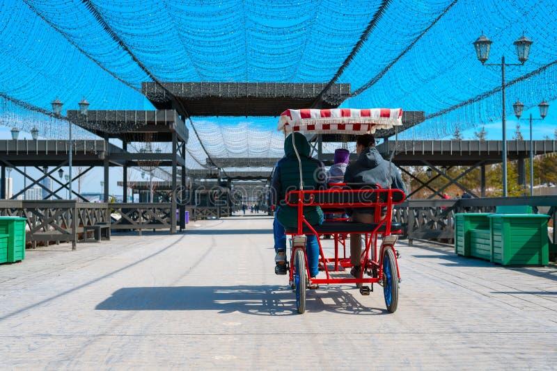 La familia monta un coche de cuatro ruedas en una trayectoria de la bici en la costa en la ciudad de Kazán Vacaciones de verano,  fotografía de archivo libre de regalías
