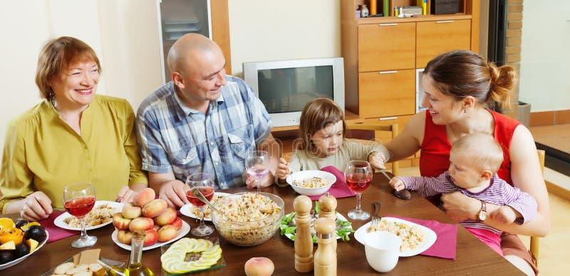 La familia multigeneración feliz comunica sobre la tabla imagenes de archivo
