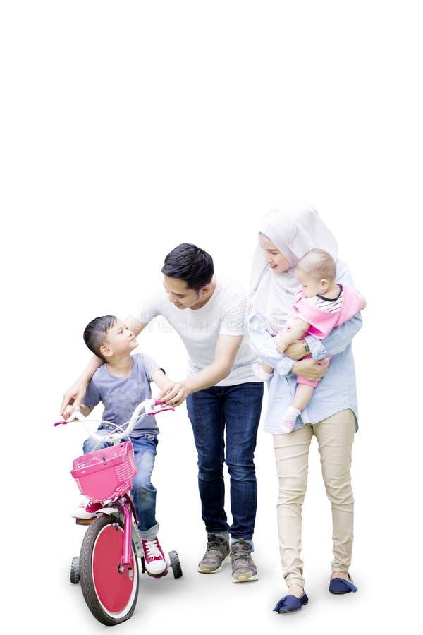 La familia musulmán ayuda a su hijo a montar la bicicleta imagenes de archivo