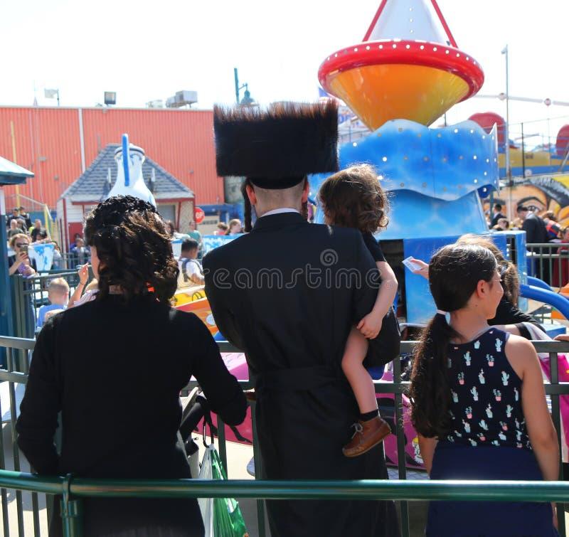 La familia ortodoxa jud?a goza al aire libre durante pascua jud?a en Coney Island Luna Park en Brooklyn, Nueva York foto de archivo libre de regalías