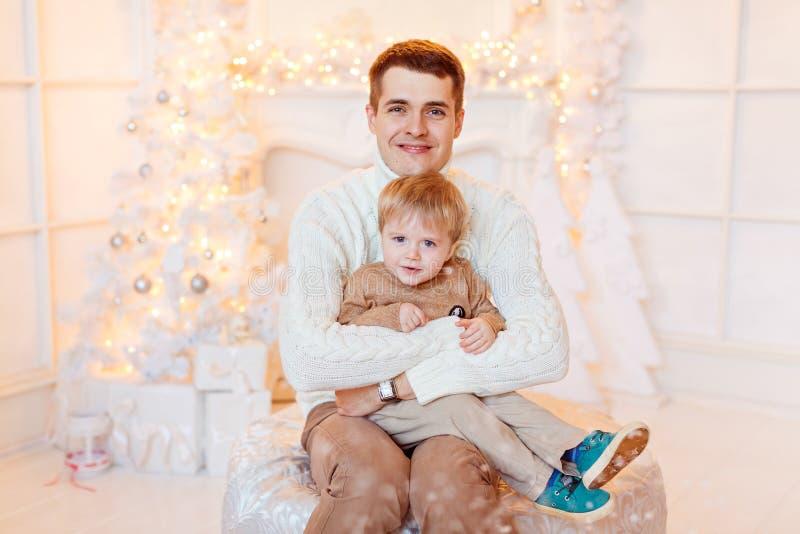 La familia - padre e hijo en abrazo brillante de la ropa en una parte posterior foto de archivo