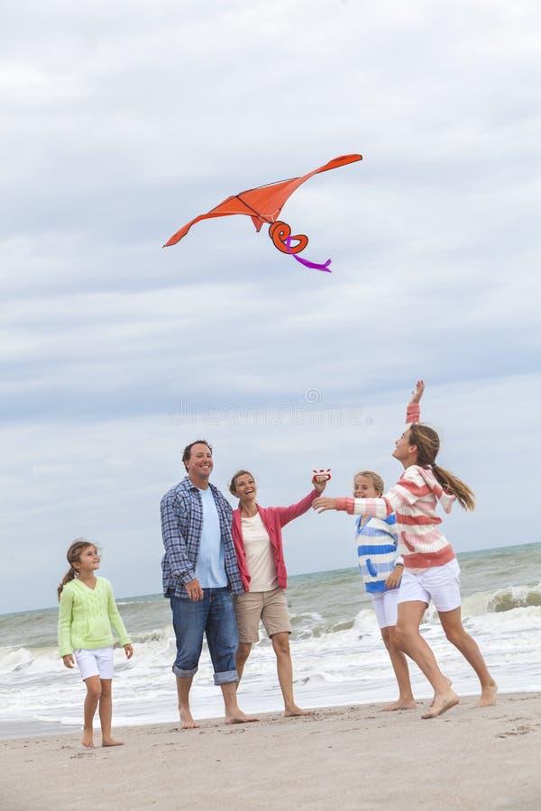 La familia Parents a los niños de la muchacha que vuelan la cometa en la playa fotografía de archivo libre de regalías
