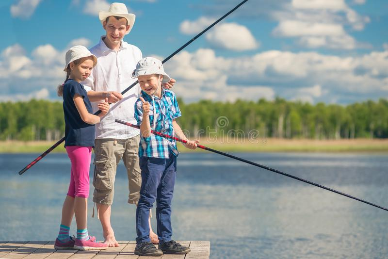La familia pasa tiempo en la pesca, gente en el embarcadero imagen de archivo