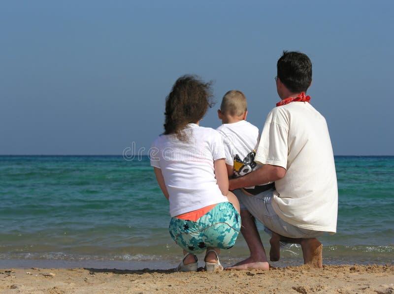 La familia posterior de tres se sienta en la playa imagen de archivo