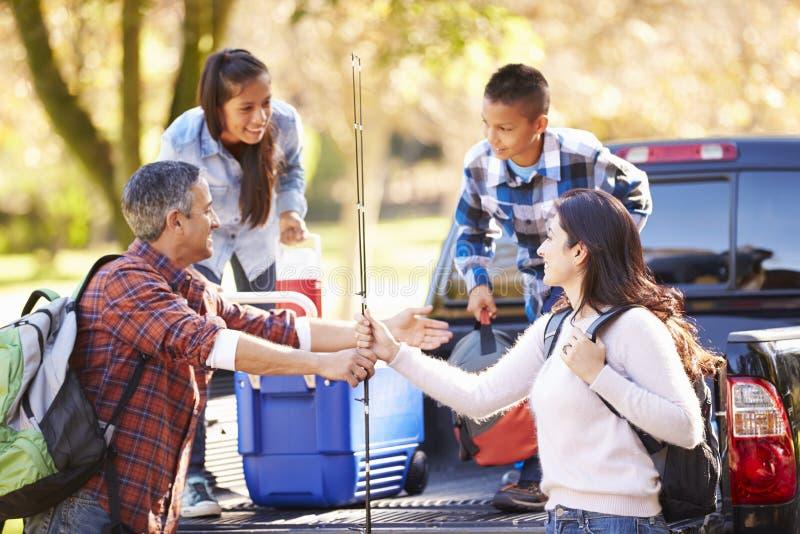 La familia que desempaqueta coge el camión en acampada imagen de archivo