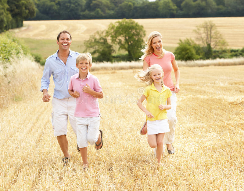 La familia que se ejecutaba junta con verano cosechó F imagen de archivo