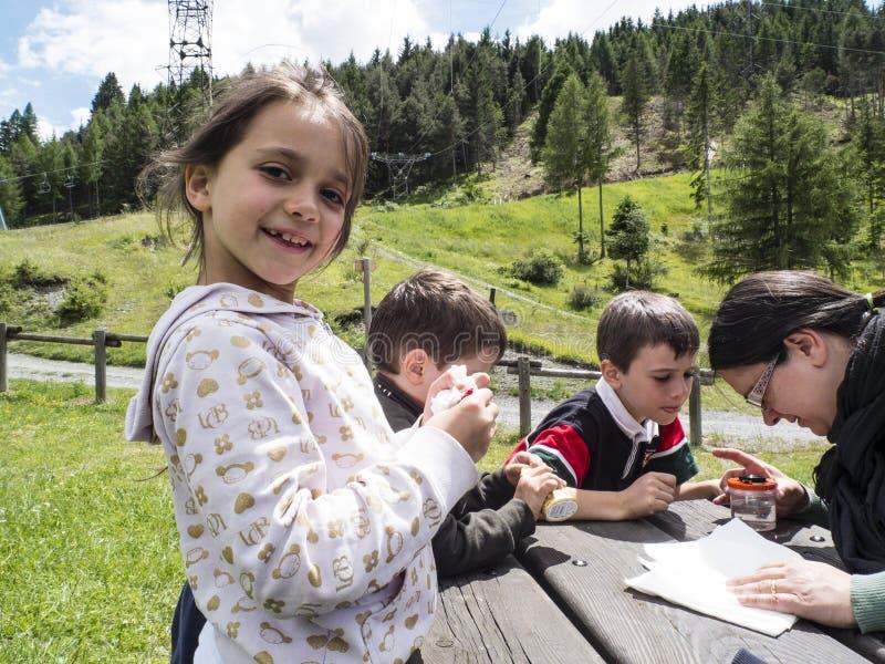 La familia que se sienta en el banco en las montañas es feliz imagen de archivo