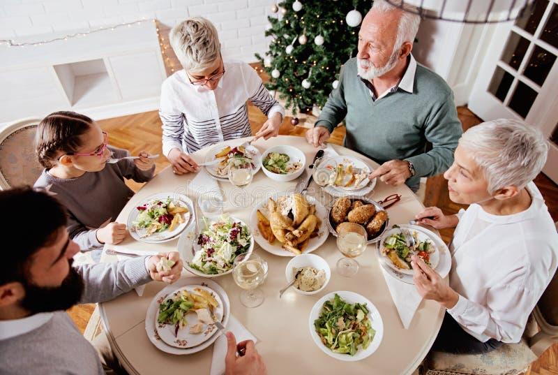 La familia recolectó durante días de fiesta de la Navidad, celebrando, almorzando fotografía de archivo