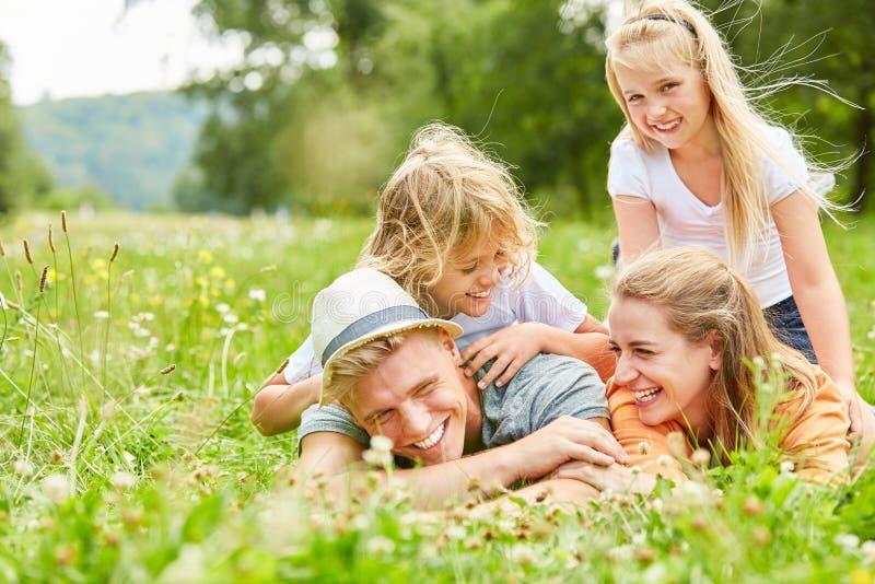 La familia se está divirtiendo en un prado del verano imagenes de archivo