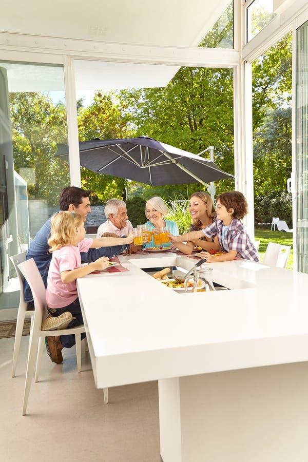 La familia se está sentando en la tabla que almuerza fotos de archivo libres de regalías