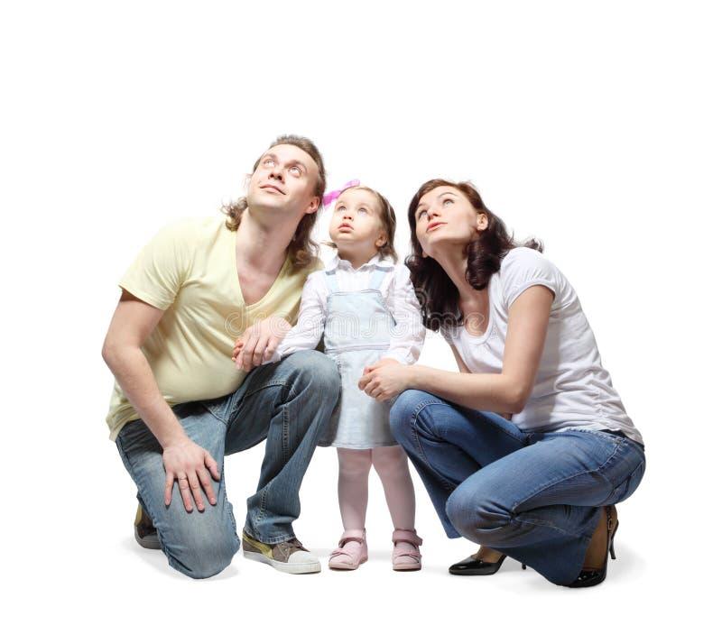 La familia se sienta, las manos del asimiento y mirada para arriba foto de archivo libre de regalías