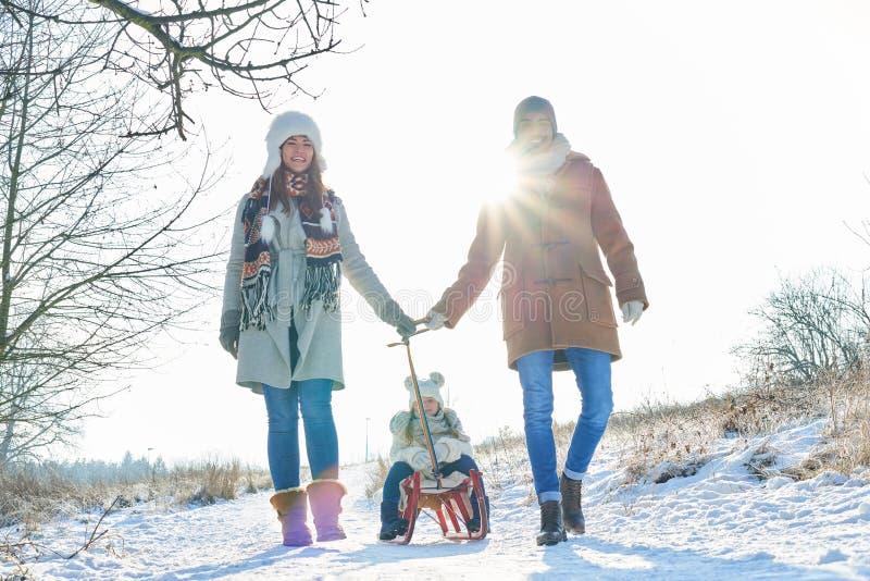 La familia toma un paseo en la nieve imagen de archivo