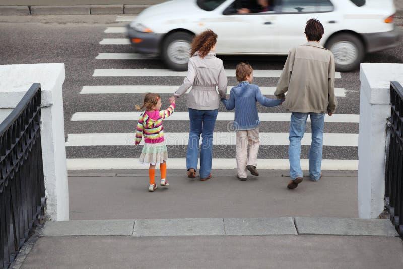 La familia va a cruzar el camino, coche blanco fotos de archivo