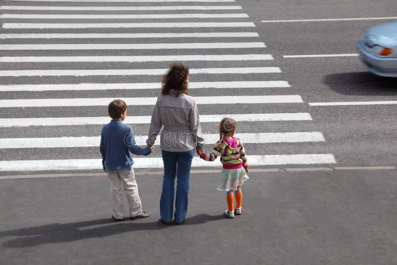 La familia va a cruzar el camino, detrás imágenes de archivo libres de regalías