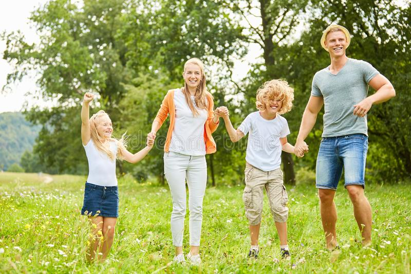 La familia y los niños están bailando feliz en el jardín imagen de archivo