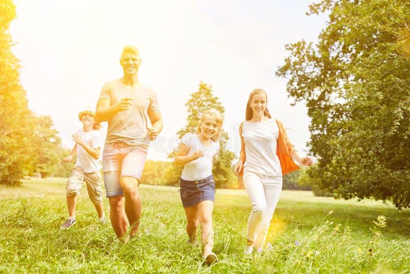 La familia y los niños felices están corriendo juntos como deporte imágenes de archivo libres de regalías