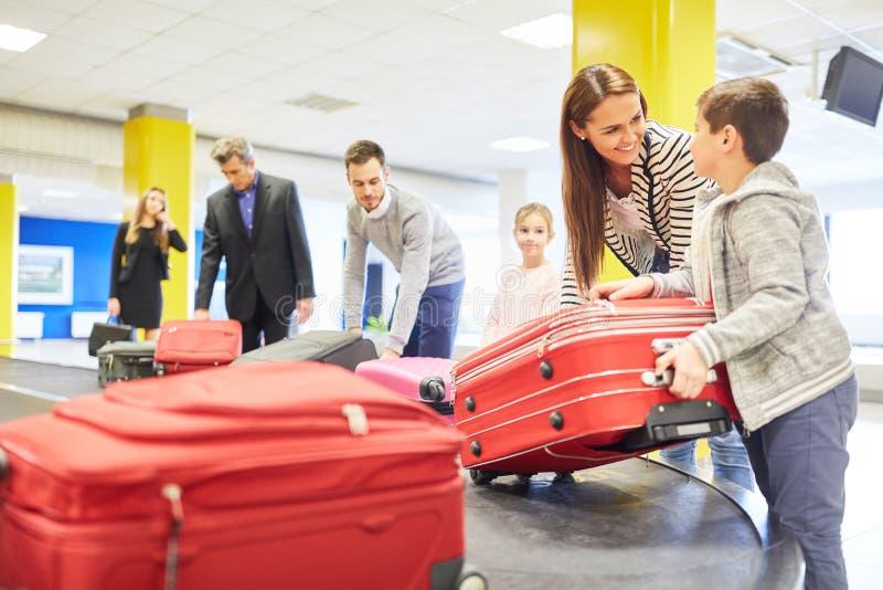 La familia y otros pasajeros cogen sus bolsos imagen de archivo