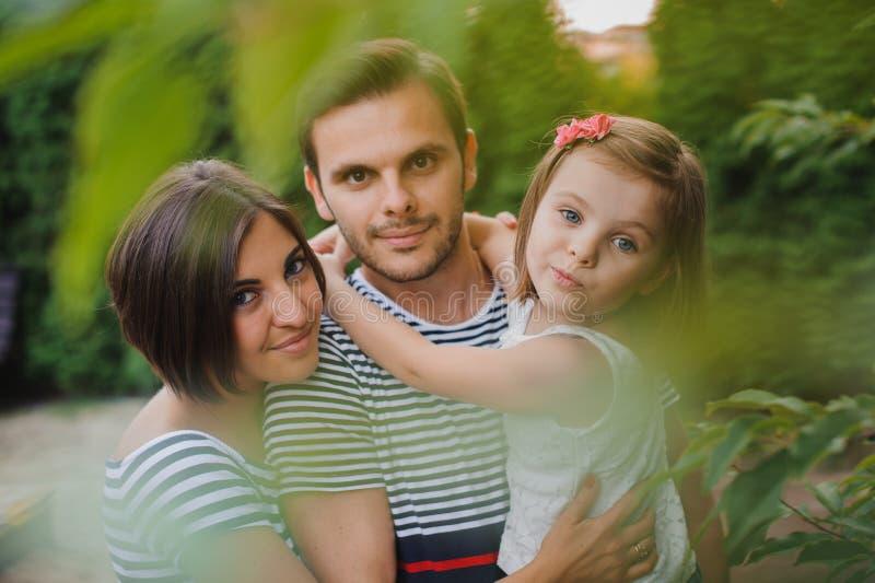 La famille active heureuse ayant l'amusement dehors se garent au printemps sur le fond vert naturel image libre de droits