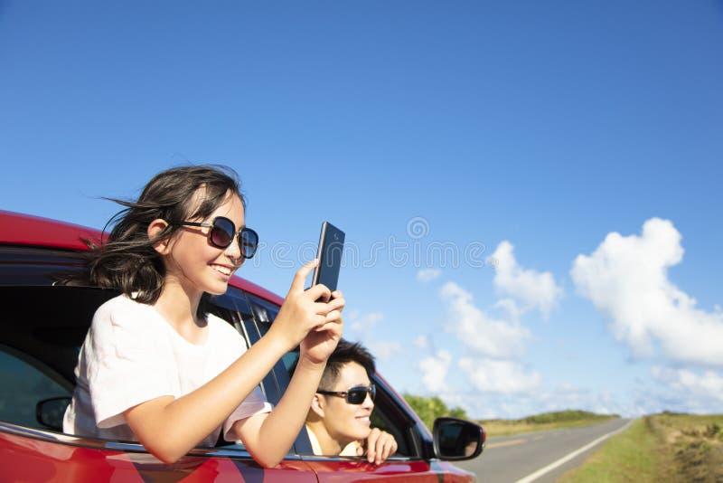 La famille apprécient le voyage par la route prenant la photo par le téléphone intelligent image libre de droits