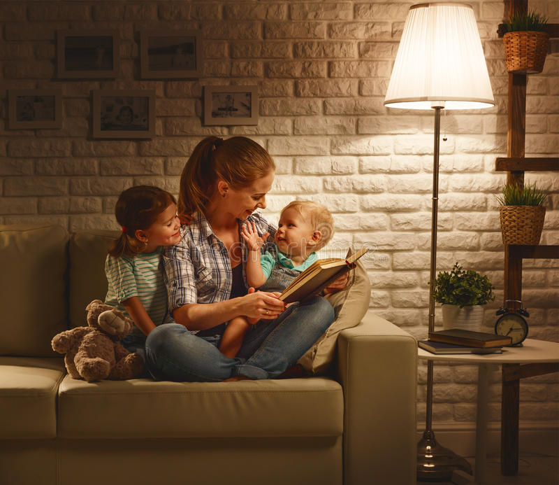 La famille avant mère allante au lit lit le livre d'enfants concernant la lampe photographie stock