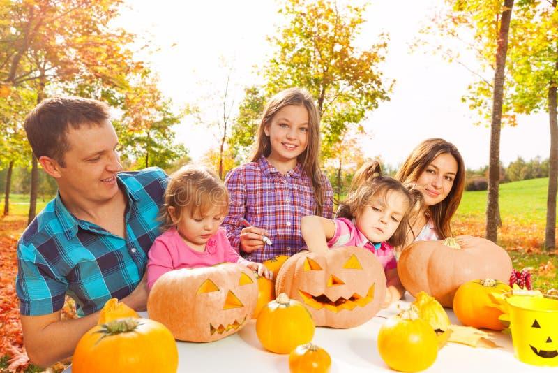 La famille avec des enfants préparent des potirons pour Halloween photographie stock libre de droits