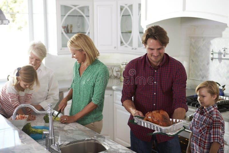 La famille avec des grands-parents font le repas de la Turquie de rôti dans la cuisine images stock