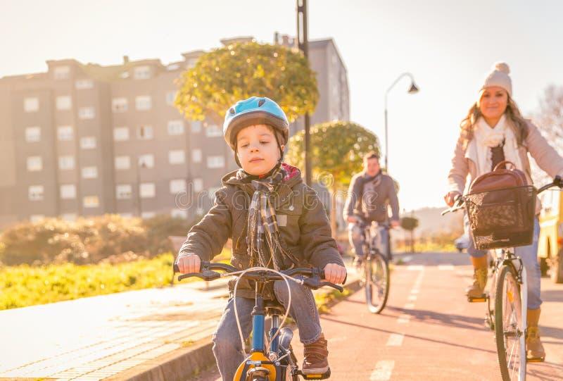 La famille avec l'équitation d'enfant va à vélo dans la ville photographie stock