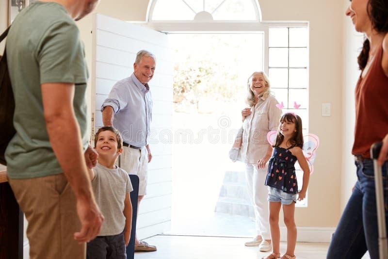 La famille blanche de trois générations quittant leur maison pour partir en vacances, longueur de trois-quarts, se ferment  image libre de droits
