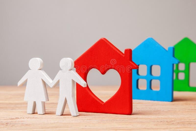 La famille choisit la maison pour acheter ou louer Couples de l'homme et femme et maisons colorées image libre de droits