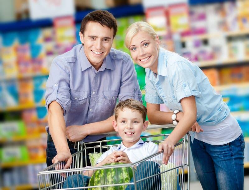 La famille conduit le chariot à achats avec la nourriture et le fils qui s'assied là photo libre de droits
