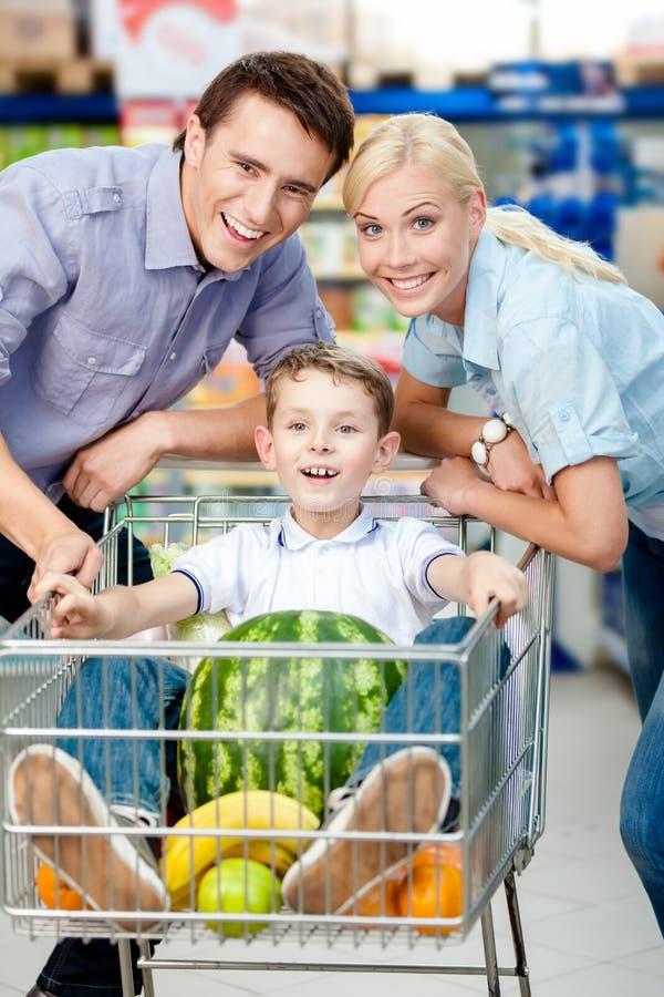 La famille conduit le chariot avec la nourriture et le garçon qui s'assied là photo libre de droits