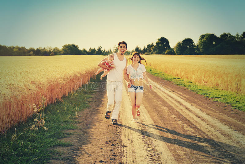 La famille courant ensemble par l'été a moissonné le champ Famille heureuse appréciant et courant ensemble dehors images stock
