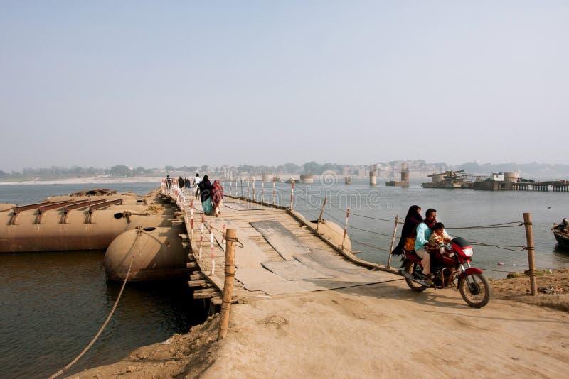 La famille a déplacé une moto par le grand pont au-dessus de la rivière le Gange photo stock