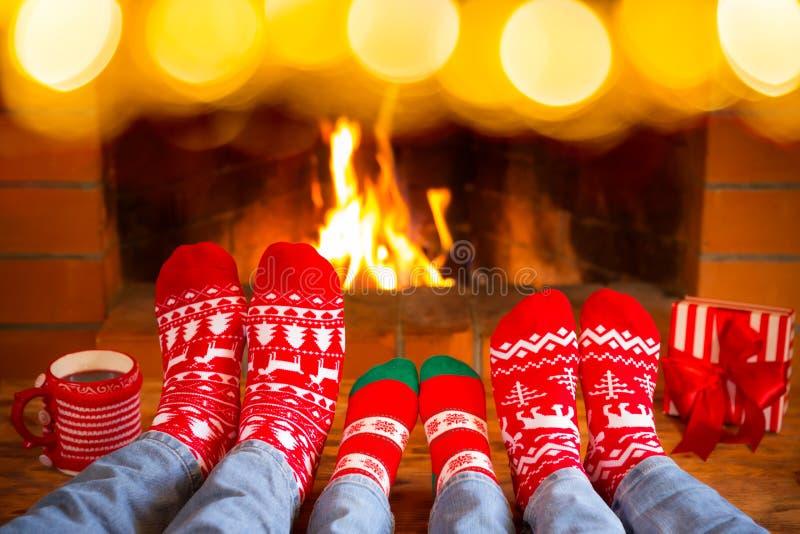 La famille dans Noël cogne près de la cheminée image stock